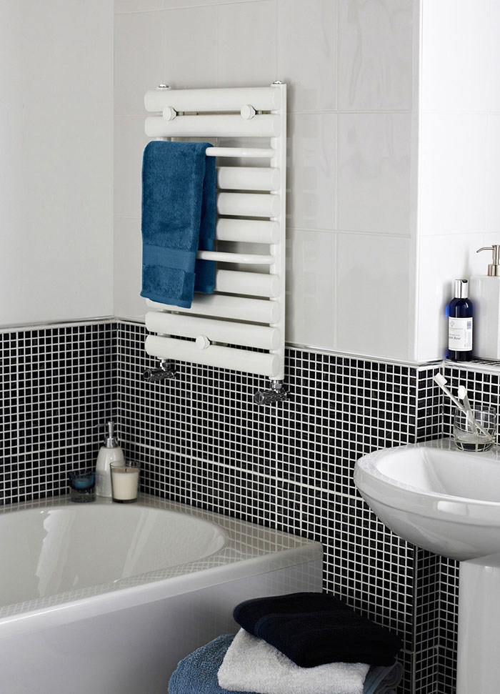 White wall mounted heated towel rail with blue towel- how to warm up your bathroom for winter