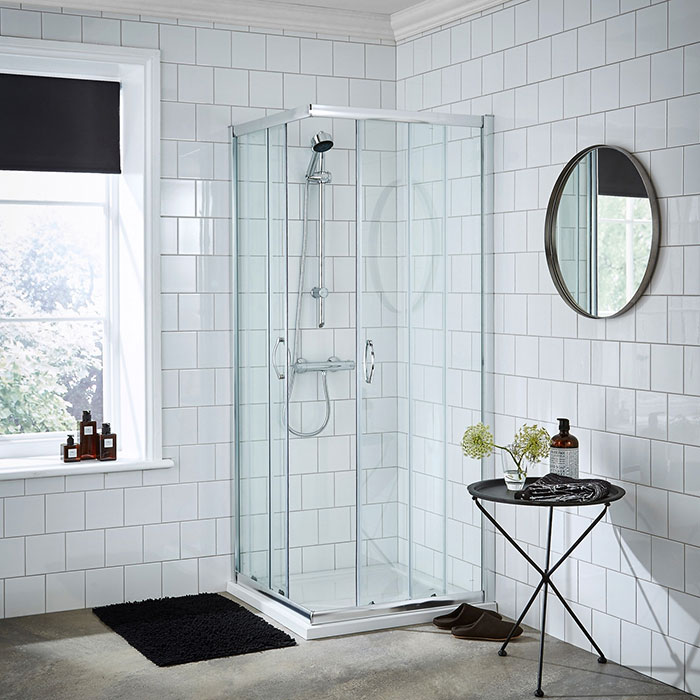 Corner entry shower enclosure with square white tiles