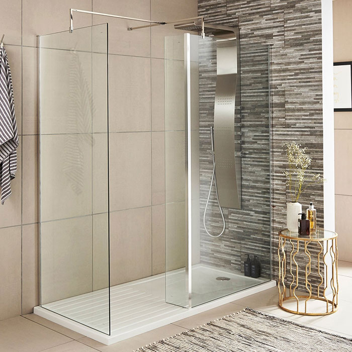 Walk in shower enclosure with shower panel and grey and beige tiles
