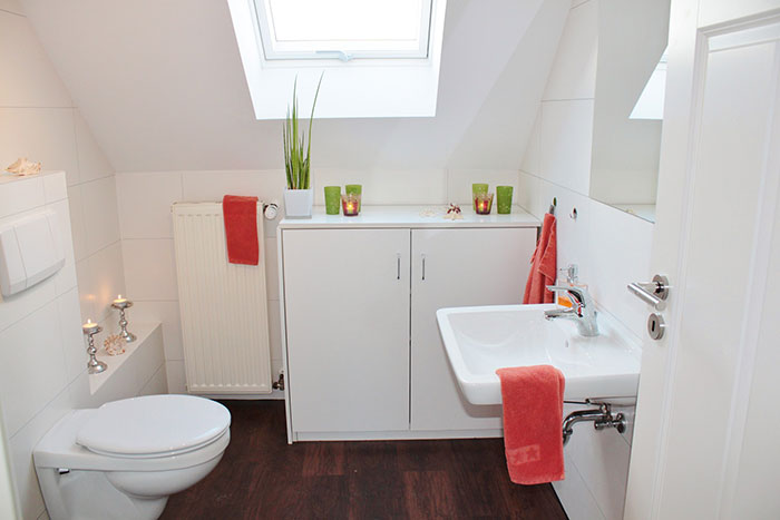 White bathroom with orange accessories